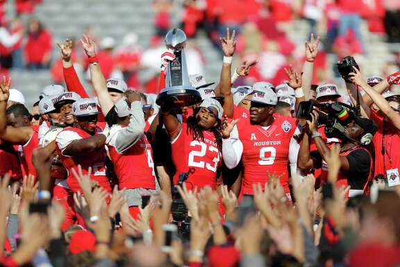 Houston Cougars safety Trevon Stewart (23), shown with the American Athletic Conference Champion trophy, celebrates with teammates after the Cougars defeated the Temple Owls 24-13 in the inaugural game played at TDECU Stadium Saturday, Dec. 5, 2015, in Houston, Texas. ( Gary Coronado / Houston Chronicle )