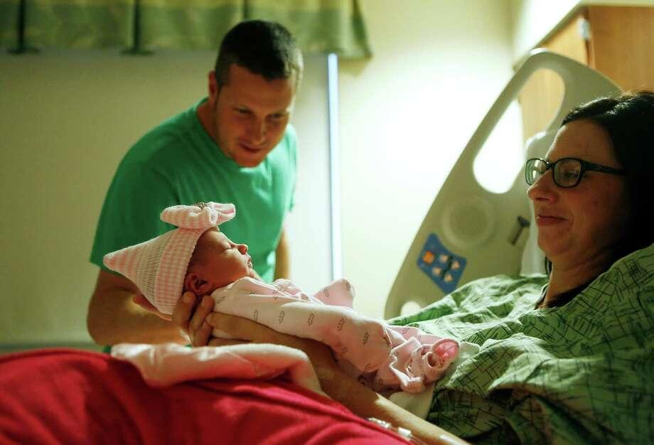 Jason and Randi Jackson are smitten with their newborn baby girl, Kollins, on Tuesday. Photo: Mark Mulligan, Staff / © 2015 Houston Chronicle