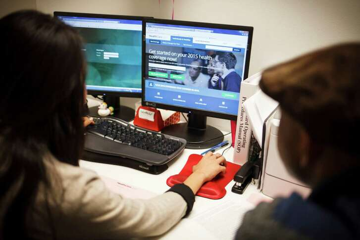 A counselor helps a man look for insurance during open enrollment on HealthCare.gov in Houston, Nov. 15, 2014. Some features are still to be added as the government tries to improve the website used to help people select health plans through the Affordable Care Act. (Michael Stravato/The New York Times)