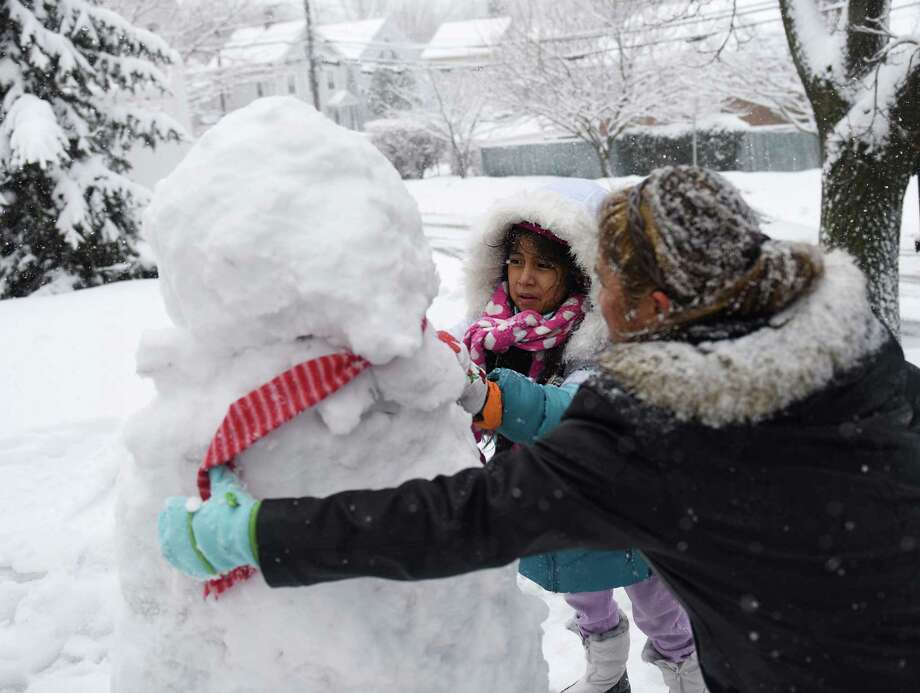 Isabel Huyhua and her daughter, Hillary Huyhua, 7, put a scarf on a snowman outside of their house in the Byram last March. While the ground outside is green now, future winter storms will give residents a chance to build snow sculptures to enter into the town contest. Photo: Tyler Sizemore / Tyler Sizemore / Greenwich Time
