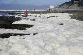 Foam from a storm surge washes up on shore on Ocean Beach Friday, Dec. 11, 2015, in San Francisco. A high surf warning remains in place in Northern California. The National Weather Service says the biggest storm of the season should quiet down in the Sierra Nevada before kicking back up Saturday. (AP Photo/Marcio Jose Sanchez)