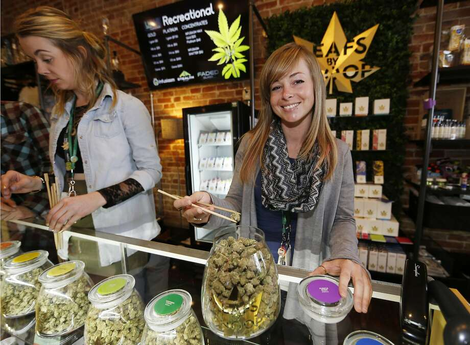 In this Dec. 18, 2015, photograph, LivWell store manager Carlyssa Scanlon shows off some of the products available in the marijuana line marketed by rapper Snoop Dogg in one of the marijuana chain's outlets south of downtown Denver. Photo: David Zalubowski, Associated Press