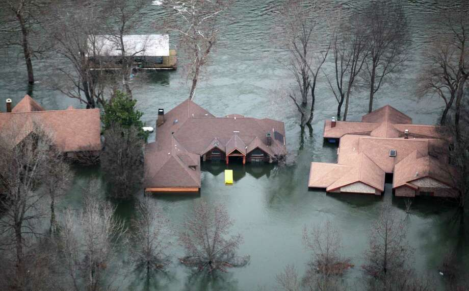 In this Tuesday, Dec. 29, 2015 photo, floodwaters from Lake Taneycomo surrounded several homes in a Branson, Mo., neighborhood after a record amount of water was released from the Table Rock Lake Dam. (Nathan Papes/The Springfield News-Leader via AP) MANDATORY CREDIT Photo: Nathan Papes, MBO / Springfield News-Leader