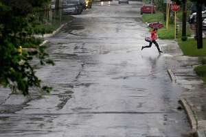 An umbrella-clad individual makes a leap over a puddle of water on Howard Street as thunder storms loomed over the city on Friday, Apr. 17, 2015. (Kin Man Hui/San Antonio Express-News)