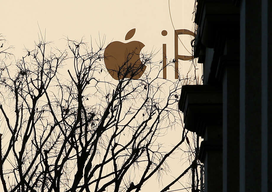 An Apple billboard looms over a street in Milan, Italy. Apple has agreed to pay Italy about $350 million in taxes for several past years, prosecutors say.  Photo: Antonio Calanni, STF / AP