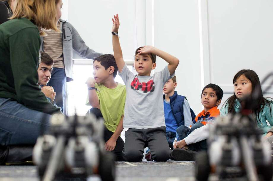 Young minds and how well they are served by education will be a major topic for the Express-News Editorial Board in 2016, with a focus on San Antonio Independent School District. Masen Olivares, 7, raises his hand to ask a question during a LEGO Mindstorm Robotics workshop at the Parman Branch Library in December. The children received mentoring from members of the Reagan High School Robotics Team. Photo: Carolyn Van Houten /Carolyn Van Houten / 2015 San Antonio Express-News