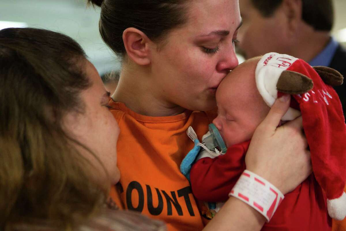 Roberta Cortopassi, an inmate at the Harris County Jail, hugs her 26-day-old baby Gionni during a Christmas event organized by the nonprofit Navidad en el Barrio. Cortopassi also opened presents with her nephew.