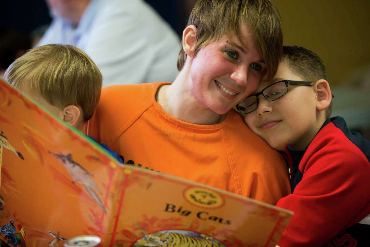 Tika English shares a moment with her son Chance English, 9, while reading during a belated Christmas event for Harris County Jail inmates.