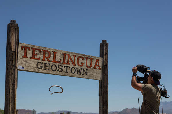 "A videographer for Original Productions films a rattlesnake falling from the ""Terlingua Ghostown"" sign at the entrance of the town on April 21, 2015.  The videographer requested that the rattlesnake be placed on top of the sign for a shot.  The snake fell approximately seven feet onto rocks moments after being placed on the sign.  The videographer's name was withheld by Adam Bradley, a producer with Original Productions."
