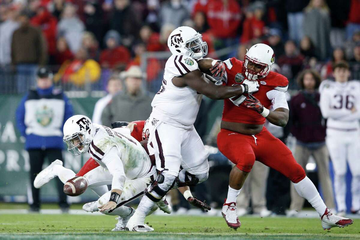 NASHVILLE, TN - DECEMBER 30: Jake Hubenak #7 of the Texas A&M Aggies fumbles the ball while being sacked by the Louisville Cardinals in the second half of the Franklin American Mortgage Music City Bowl at Nissan Stadium on December 30, 2015 in Nashville, Tennessee.
