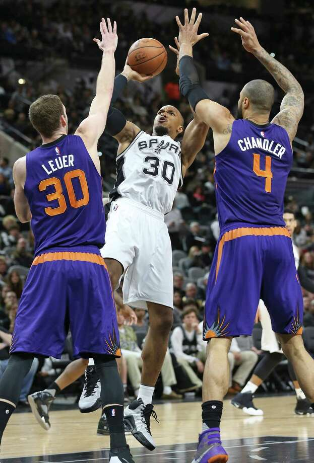 David West takes  a fade away jump shot over Jon Leuer and Tyson Chandler as the Spurs host the Suns at the AT&T Center on December 30, 2015. Photo: TOM REEL, STAFF / SAN ANTONIO EXPRESS-NEWS / 2015 SAN ANTONIO EXPRESS-NEWS