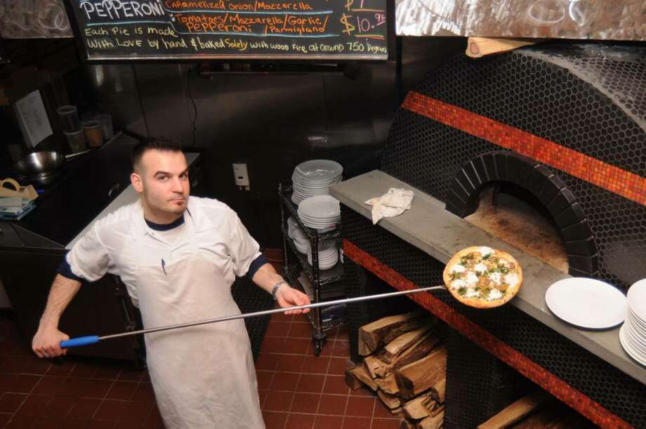 Matt Stanziato, owner of Stanziato's Wood Fired Pizza , at 35 Lake Avenue Extention, in Danbury, CT,  takes a sauage pizza out of his wood fired brick pizza oven on Wednesday, March 31, 2010. Photo: Jay Weir / The News-Times