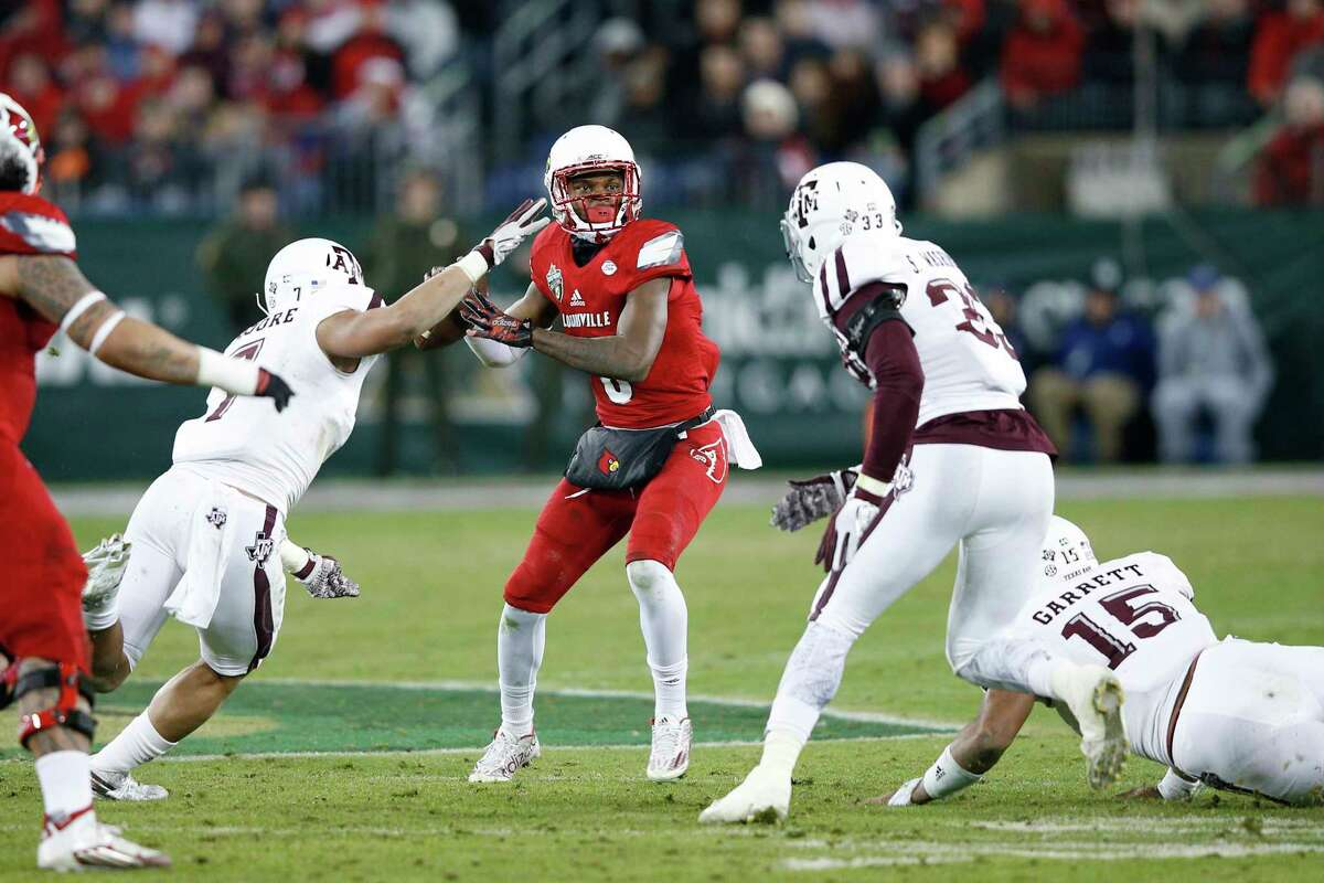 NASHVILLE, TN - DECEMBER 30: Lamar Jackson #8 of the Louisville Cardinals looks to pass while under pressure from the Texas A&M Aggies in the second half of the Franklin American Mortgage Music City Bowl at Nissan Stadium on December 30, 2015 in Nashville, Tennessee.