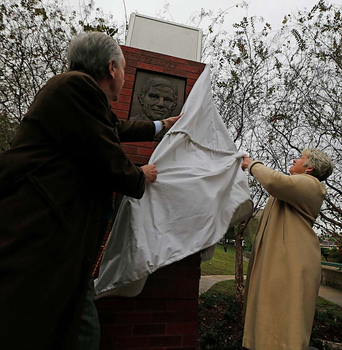 Davis Jones left, and Mayor Annise Parker right, unveil one of two bronze relief panels depicting former U.S. Commerce Secretary Robert Mosbacher, Sr. during the gifting ceremony, the commemorative panels are located near the Preston Street Bridge in Sesquicentennial Park Wednesday, Dec. 30, 2015, in Houston. The bridge has been renamed as the Robert A. Mosbacher, Sr., Memorial Bridge.