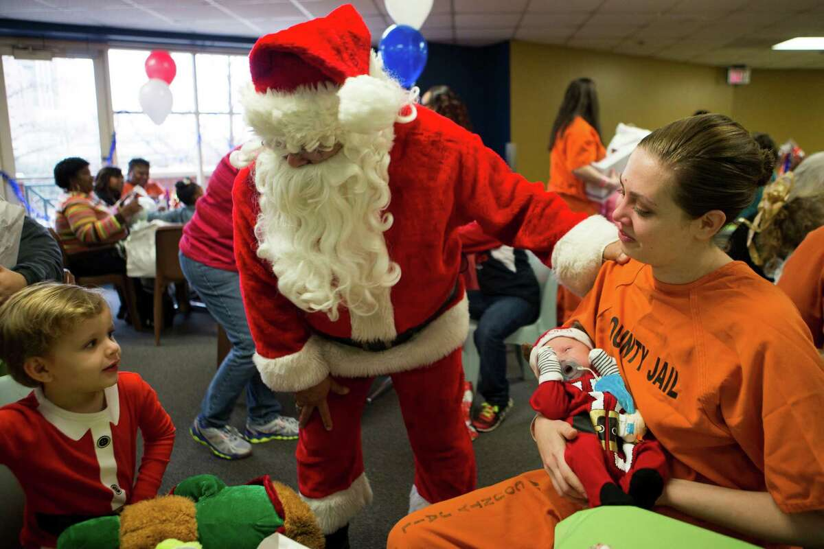 Felix Vargas, left, 3, is greeted by Santa Claus during a visit to the Harris County Jail to spend time with his aunt Roberta Cortopassi, right, 24. Cortopassi is an inmate at the jail and part of a program that gave her the opportunity to be with family. Wednesday, Dec. 30, 2015, in Houston.