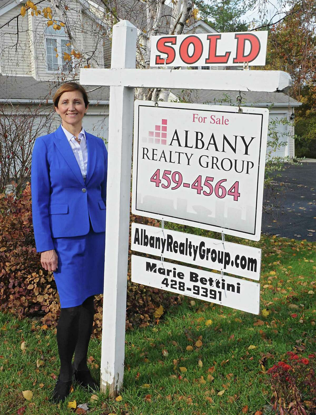 Marie Bettini stands next to her real estate sign at 1082 Sterling Ridge Dr. on Thursday, Oct. 29, 2015 in Rensselaer, N.Y. (Lori Van Buren/Times Union) ORG XMIT: MER2015102916042525