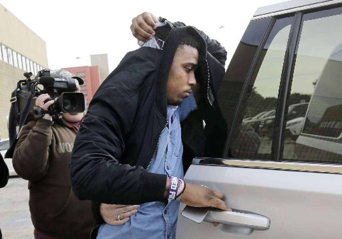 TCU quarterback Trevone Boykin holds a jacket over his head as he is escorted from a detention center after he was released on bail, Thursday, Dec. 31, 2015, in San Antonio. Police charged Boykin with felony assault of a police officer stemming from a bar fight early Thursday morning. TCU football coach Gary Patterson has suspended Boykin for Saturday's Alamo Bowl game against Oregon.
