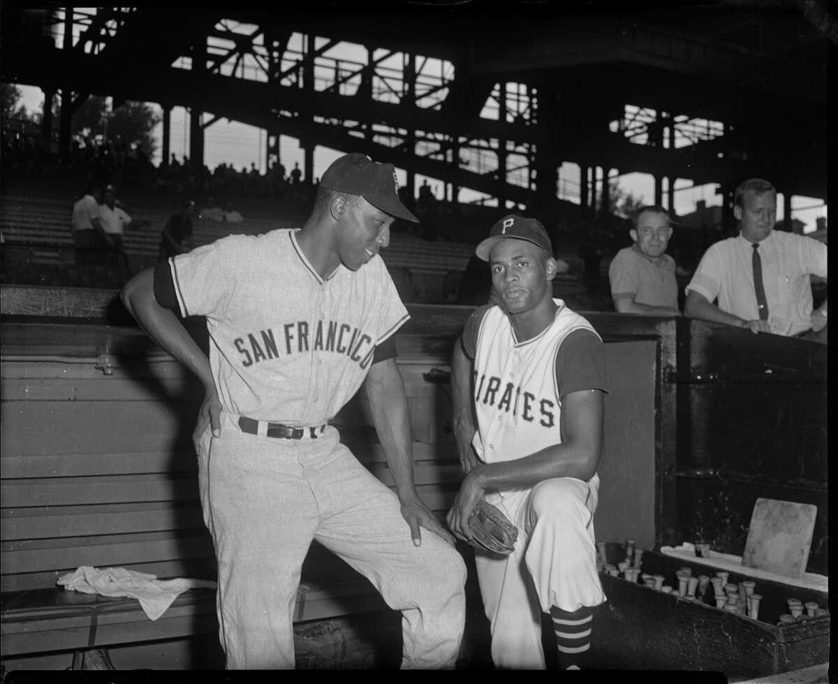 San Francisco Giants baseball player Willie McCovey with Pittsburgh Pirates player Roberto Clemente posing in front of dugout at Forbes Field, Pittsburgh, Pennsylvania, circa 1960.