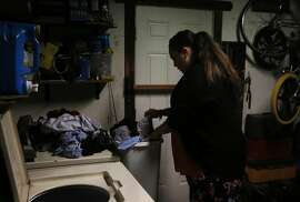 Sonya Tafoya, 40, does laundry in the family home she shares with her partner Victor Martinez Dec. 30, 2015 in Pittsburg, Calif. Tafoya is born and raised in Pittsburg. She has a criminal history and she says it was her last stint in jail that helped straighten her out. Tafoya hasn't been in trouble since the early 2000s.