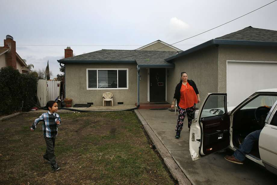 From left, Kazsh Martinez, 6, runs to the car with his parents, Sonya Tafoya and Victor Martinez, outside their Pittsburg home. Photo: Leah Millis, The Chronicle