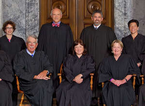 The Washington state Supreme Court as composed in 2015. From left: Justice Mary Fairhurst, Justice Sheryl Gordon McCloud, Associate Chief Justice Charles Johnson, Justice Charles Wiggins, Chief Justice Barbara Madsen, Justice Steven Gonzalez, Justice Susan Owens, Justice Mary Yu and Justice Debra Stephens.