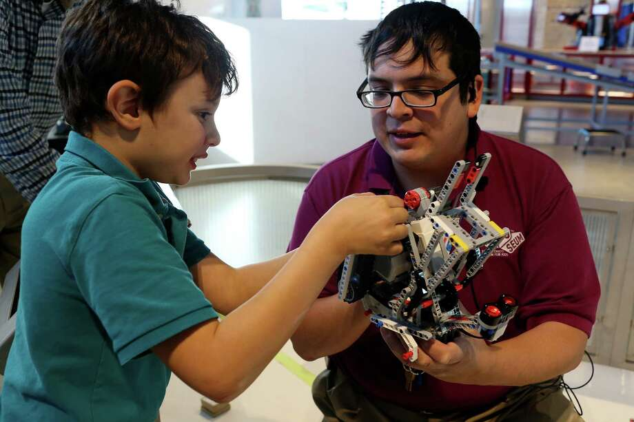 DoSeum Discovery Leader Henry Lozano helps Morris Lichtenstein, 8, with a robot Thursday, Nov. 18, 2015. Lozano is known for his exuberant personality and ability to draw children out. Photo: JERRY LARA, Staff / San Antonio Express-News / © 2015 San Antonio Express-News
