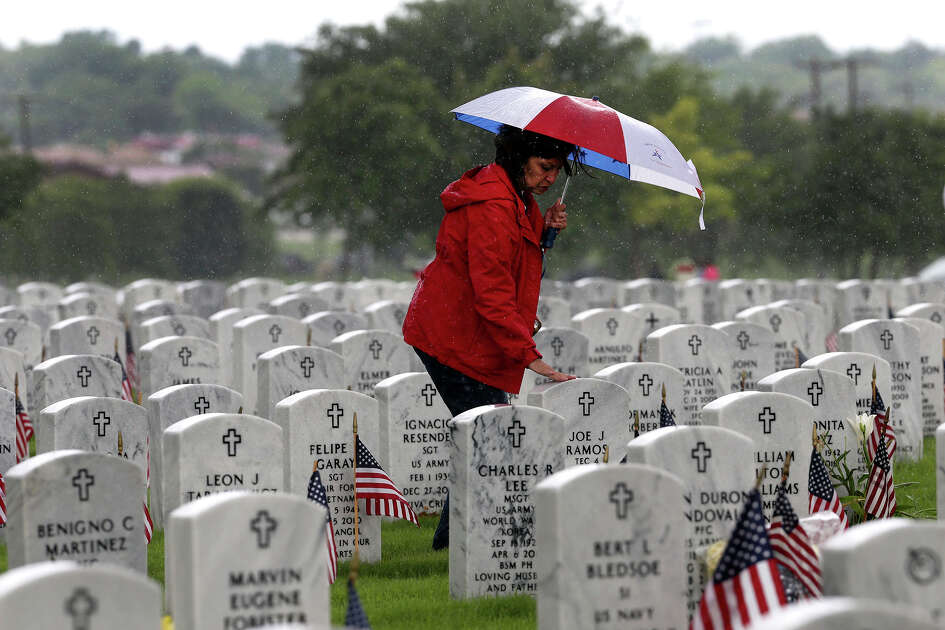 Janie Ramos touches her father's headstone after the Memorial Day ceremony Monday May 25, 2015 at Fort Sam Houston National Cemetery. Her father, Joe J. Ramos, served in the Army during World War II.