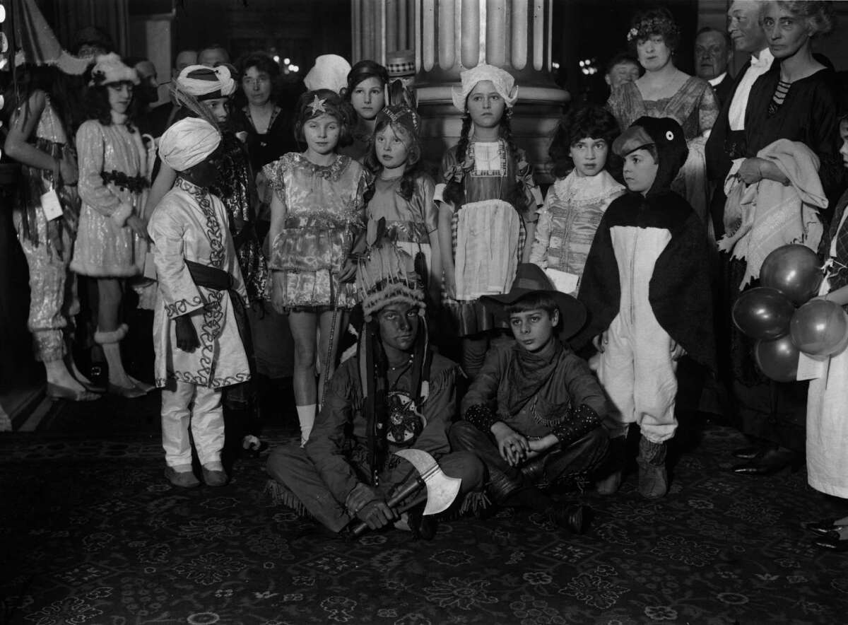 1922: A group of children dressed up for a New Year's fancy dress party in England.