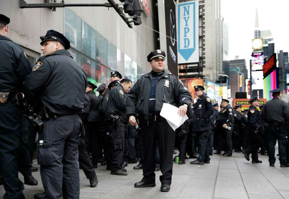 Police officers gather at the southern end of Times Square to receive their assignments for New Year's Eve in New York, Thursday, Dec. 31, 2015. Around 1 million people are expected to converge on Times Square for the annual New Year's Eve celebration. This year's festivities will also be attended by nearly 6,000 New York City police officers, including members of a specialized counterterrorism unit. Photo: Seth Wenig, AP / AP