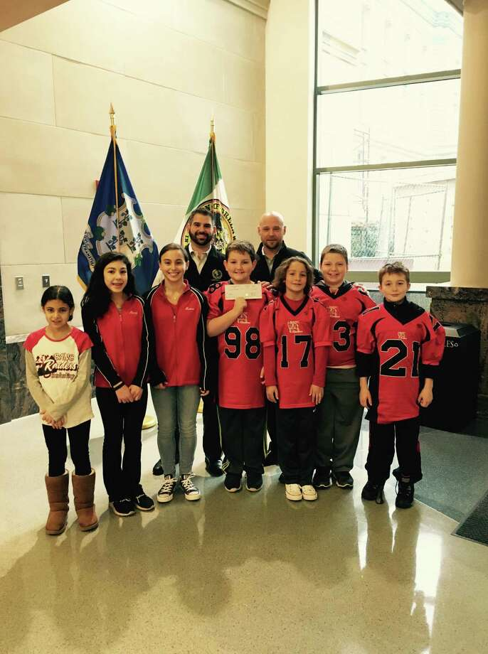 In back, GPD Police Officers Dan Paladino and Keith Hirsch join BANC Raiders kids, from left, Christina Brunetti, Alexa Brunetti, Maeve Petrizzi -Dolan, James Roina, Archer Manning, Roman Pennella and Patrick Lane for a presentation of a $500 check to support the program. Photo: / Contributed Photo