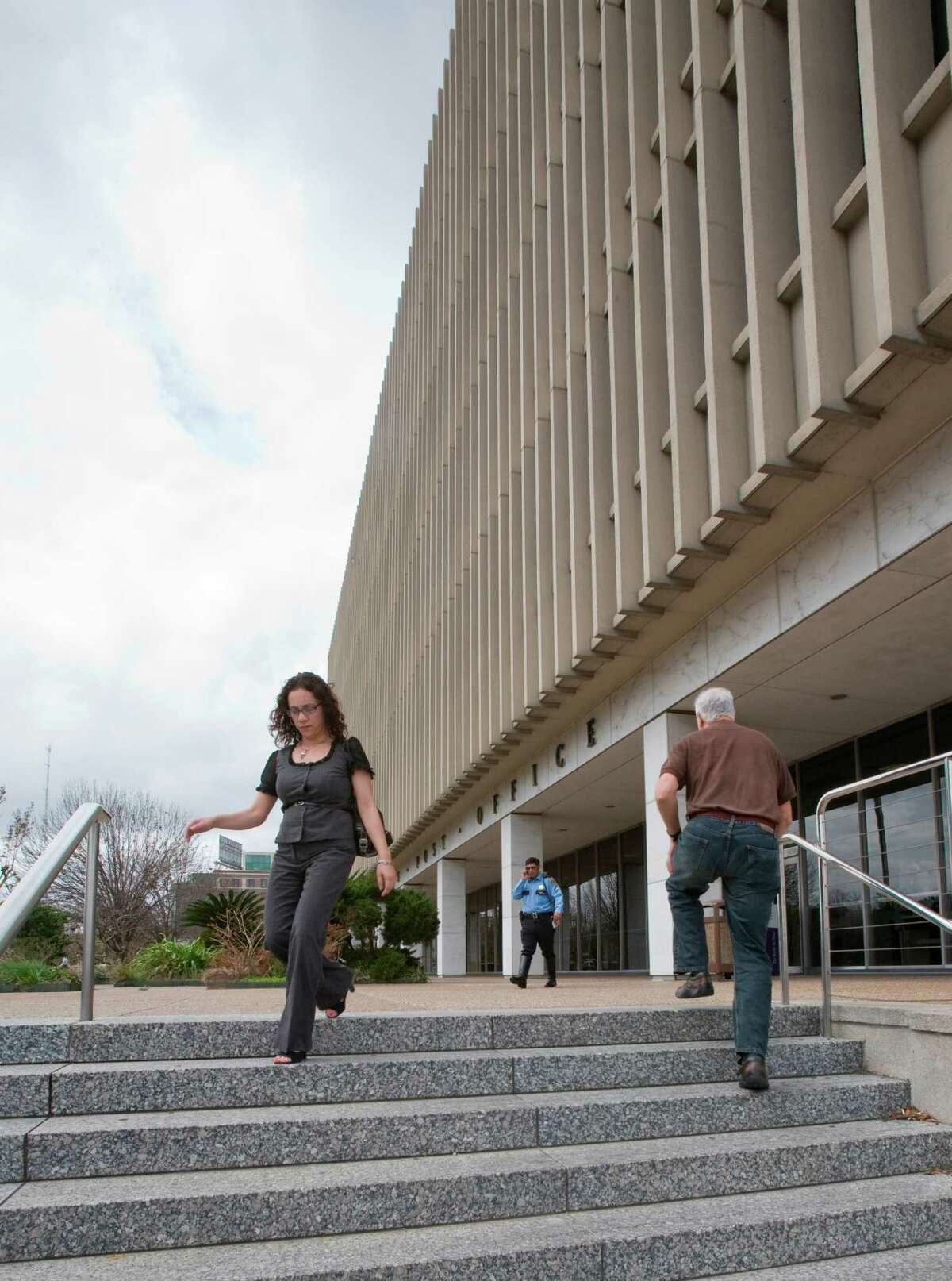Lisa Pantoja walks down the steps of the downtown post office. The downtown Post Office is being put up for sale. Whoever buys the property must build a replacement processing facility for the postal service as well as proide a retail space in or around downtown for consumers. (Wednesday, Feb. 25, 2009, in Houston. ( Steve Campbell / Houston Chronicle)