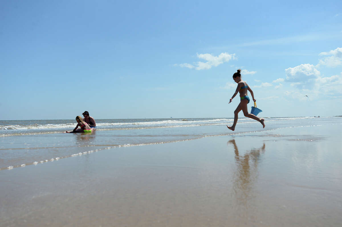 Families play on the shoreline at McFaddin Beach Monday. Dune restoration at the McFaddin National Wildlife Refuge is among the funding items on the agenda for the Commissioners Court. Photo taken Monday, June 1, 2015 Kim Brent/The Enterprise
