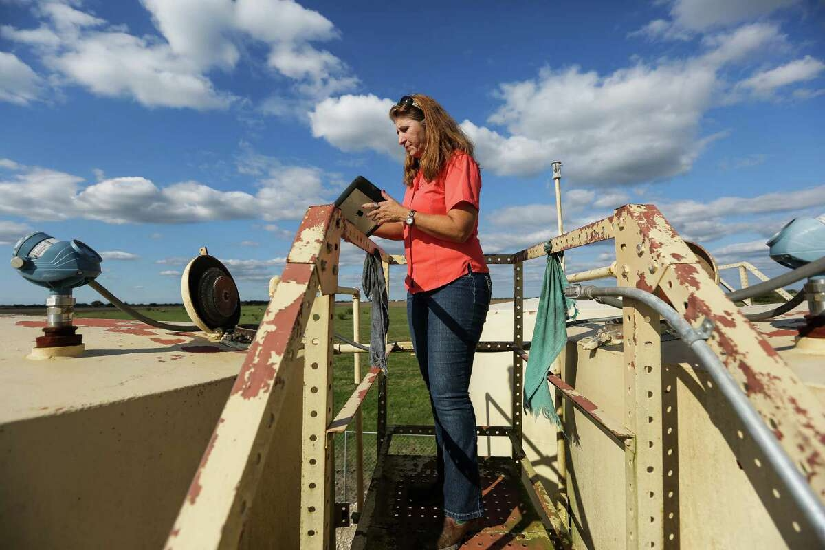Using an application created by WellAware, Gaye Hester of Welder Exploration & Production, Inc. monitors oil and water levels on a tank in Beeville in November. ( Michael Ciaglo / Houston Chronicle )