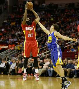 HOUSTON, TX - DECEMBER 31:  James Harden #13 of the Houston Rockets shoots over Klay Thompson #11 of the Golden State Warriors at Toyota Center on December 31, 2015 in Houston, Texas. NOTE TO USER: User expressly acknowledges and agrees that, by downloading and or using this Photograph, User is consenting to the terms and conditions of the Getty Images License Agreement. Mandatory Copyright Notice: Copyright 2015 NBAE  (Photo by Bob Levey/Getty Images)