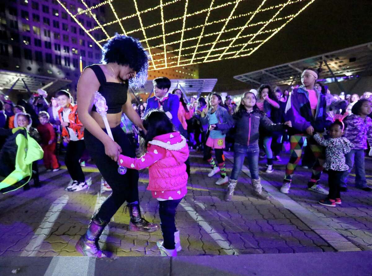 Brooklyn Bass dances with Vania Evangelio, 5,at Houston's New Year's Eve party downtown on Thursday.