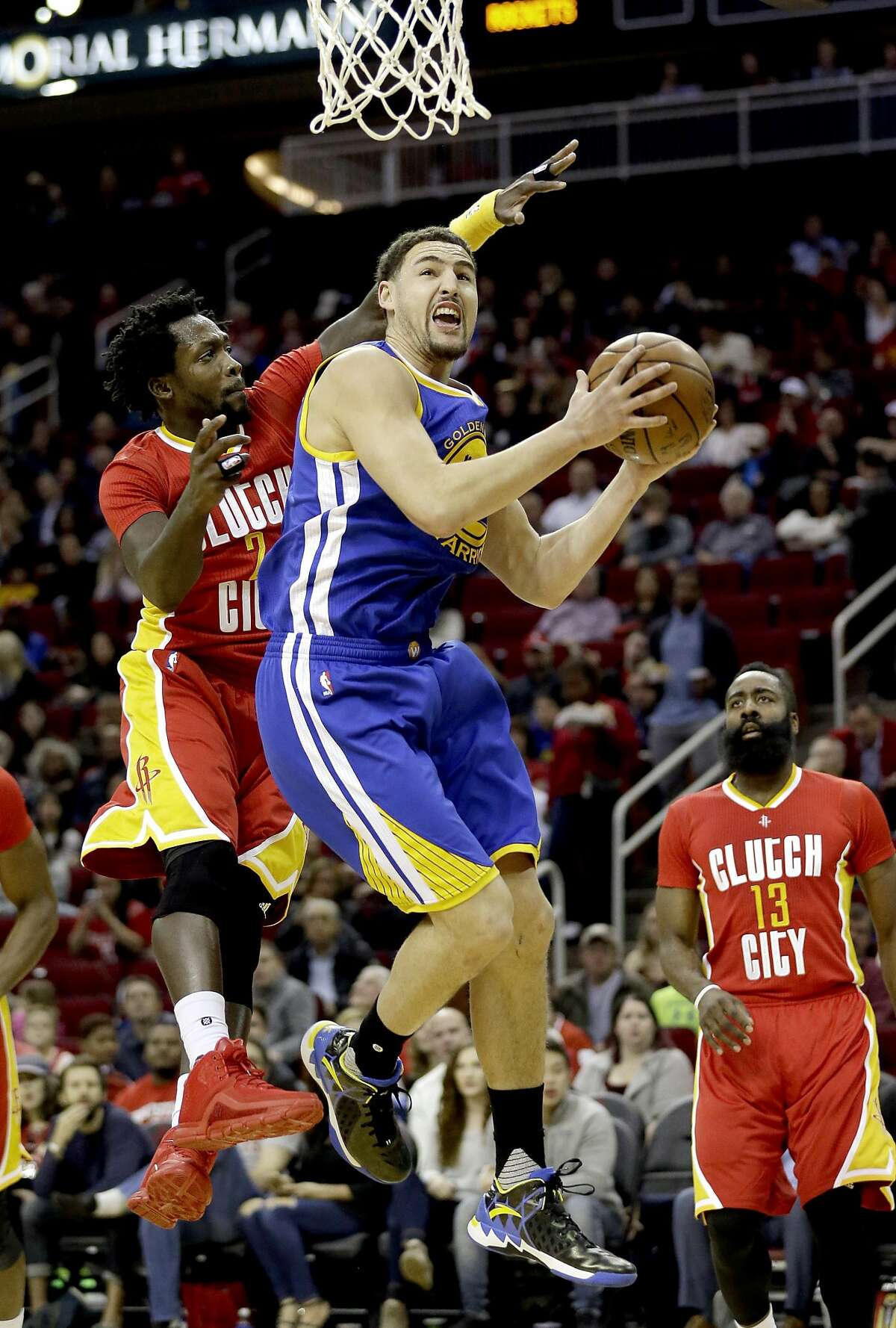 Golden State Warriors' Klay Thompson, front right, goes up to shoot as Houston Rockets' Patrick Beverley (2) defends during the first half of an NBA basketball game Thursday, Dec. 31, 2015, in Houston. (AP Photo/David J. Phillip)
