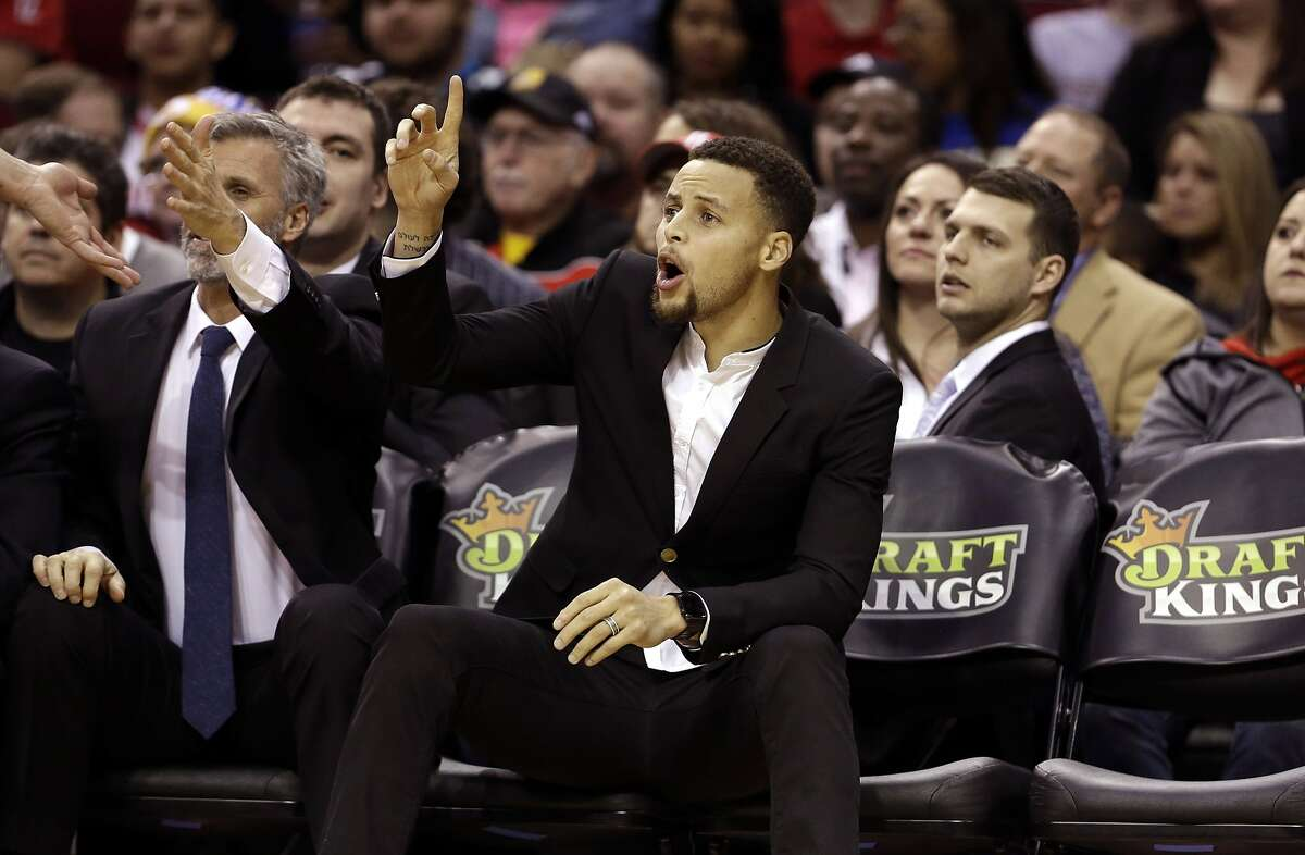 Golden State Warriors' Stephen Curry, center, yells to teammates as he sits on the bench during the first half of an NBA basketball game against the Houston Rockets Thursday, Dec. 31, 2015, in Houston. Curry is out for the second straight game with a bruised lower left leg. (AP Photo/David J. Phillip)