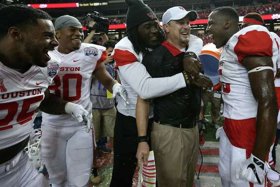 UH coach Tom Herman is surrounded by a bunch of happy Cougars after a 38-24 victory over Florida State in the Chick-fil-A Peach Bowl on Thursday.
