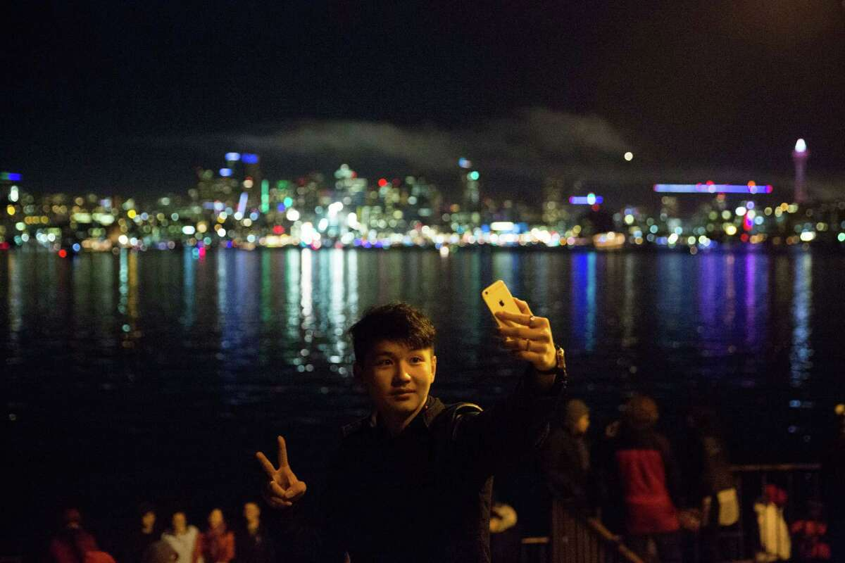 A spectator takes a selfie as smoke from the Space Needle fireworks show drifts over the city's skyline following Seattle's ringing in of the new year, at Gas Works Park on Friday, Jan. 1, 2016.