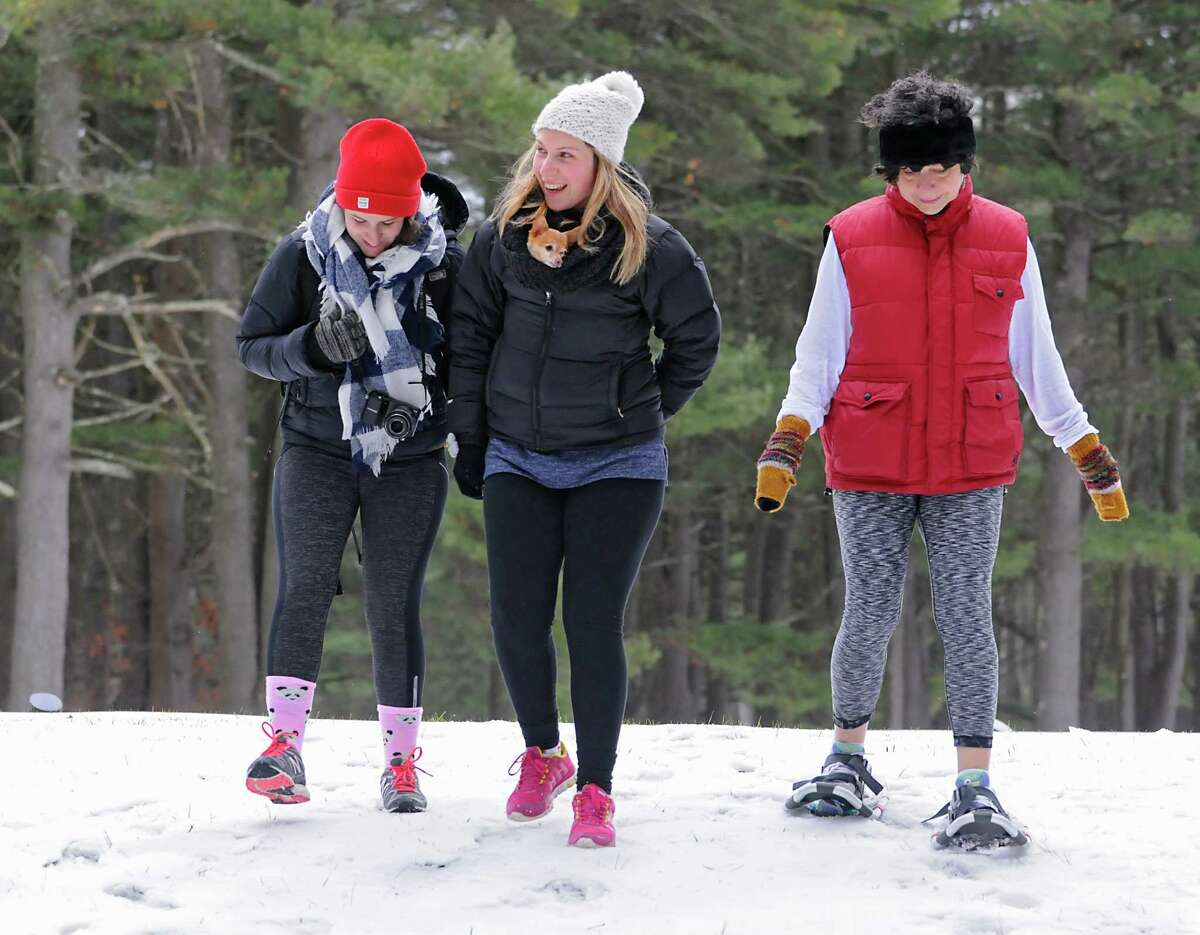 From left, Katherine Turro, Molly Turro with her dog Tinkerbell and Linda Scacco, all from West Hartford, Conn. participate in a first hike on New Year's Day at Saratoga Spa State Park on Friday, Jan. 1, 2016 in Saratoga Springs, N.Y. (Lori Van Buren / Times Union)