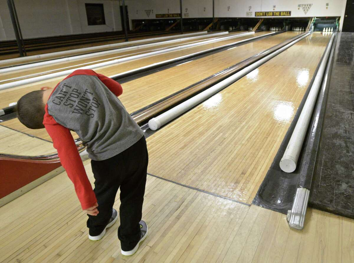 Matty Cohen, 4, from Long Island, uses a little body english to try and get his ball to move while duckpin bowling at Danbury Duckpin Lanes, on Friday, January 1, 2016.