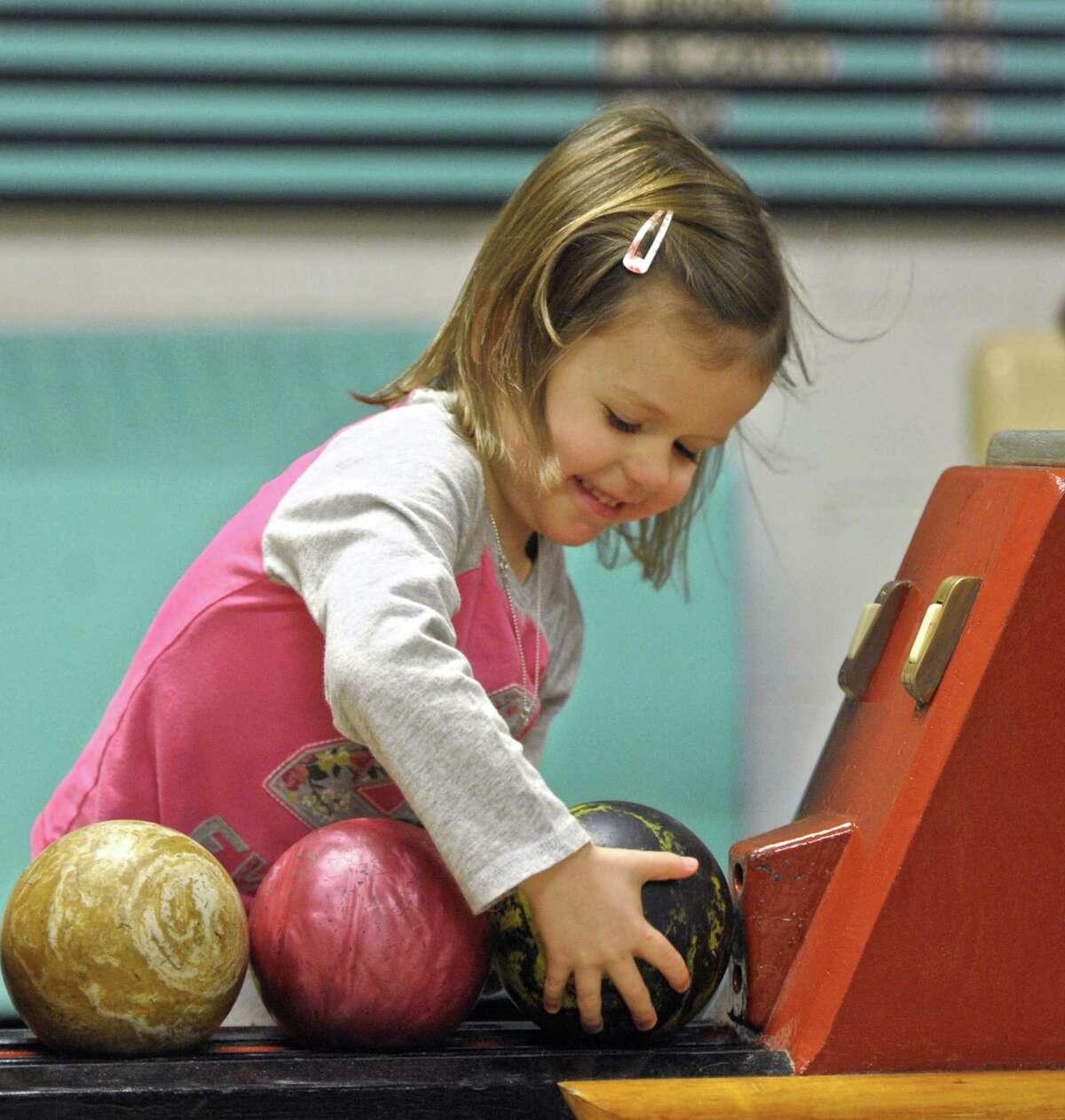 Ellie Pickard, 4, of Newtown, picks a ball while duckpin bowling at Danbury Duckpin Lanes, in Danbury, Conn, on Friday, January 1, 2016.