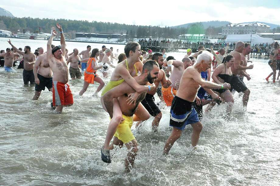 Participants run into the water and back during the annual Lake George Polar Plunge on Friday, Jan. 1, 2016 in Lake George, N.Y. (Lori Van Buren / Times Union) Photo: Lori Van Buren / 10034803A