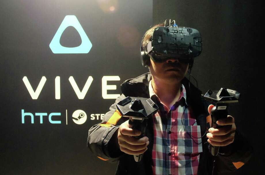 A fan wears a HTC Vive headset and holds two sensors during a promotional event held by HTC in Taipei last month. Smartphone maker HTC unveiled to Taiwanese gamers its virtual reality headset for the first time, as the company pins hopes on the new product to help revive its struggling business. Photo: Sam Yeh /AFP / Getty Images / AFP