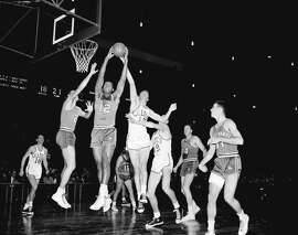 Maurice Stokes (12) of Cincinnati battles the Celtics' Tommy Heinsohn for a rebound in February 1958 at New York's Madison Square Garden. The following month, his career would end abruptly.