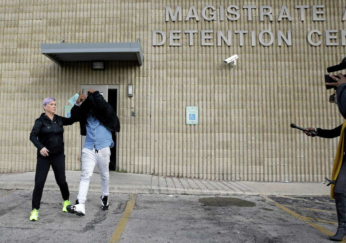 TCU quarterback Trevone Boykin, second from left, holds a jacket over his head as he is escorted from a detention center after he was released on bail, Thursday, Dec. 31, 2015, in San Antonio. Police charged Boykin with felony assault of a police officer stemming from a bar fight early Thursday morning. TCU football coach Gary Patterson has suspended Boykin for Saturday's Alamo Bowl game against Oregon. (AP Photo/Eric Gay)