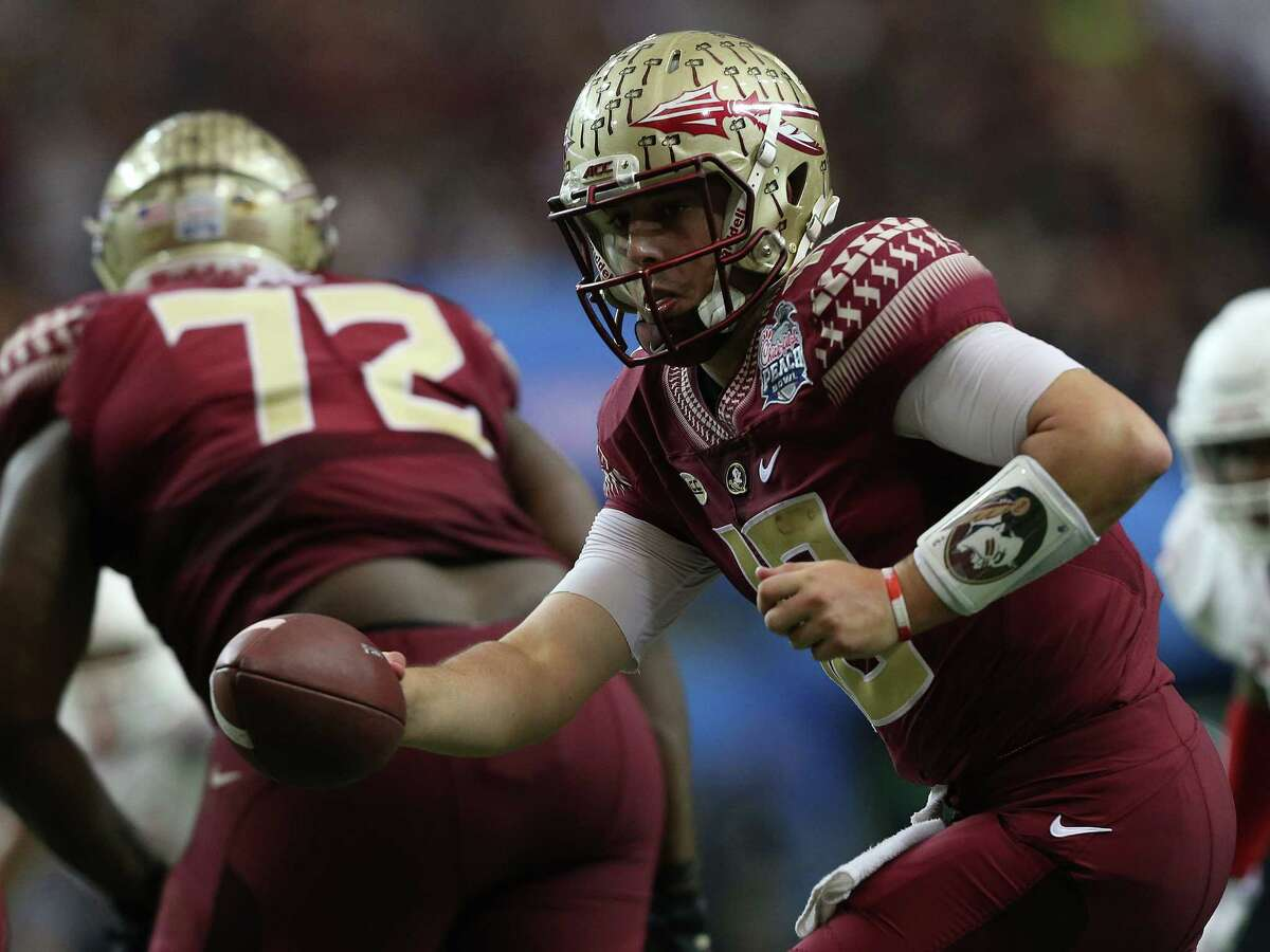 Florida State Seminoles quarterback Sean Maguire (10) dishes the ballin the second half of the Chick-fil-A Peach Bowl against Houston Cougars at the Georgia Dome on Thursday, Dec. 31, 2015, in Atlanta.