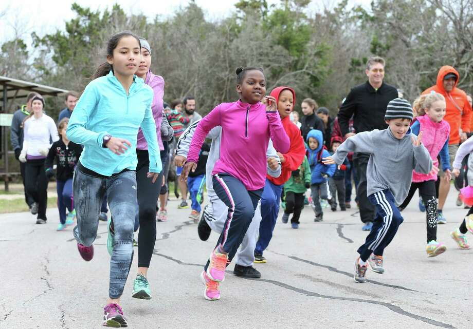 """Eventual winner Cha Chi Gonzales (left) leads from the start as kids and parents participate in a one mile """"1st Day Run"""" in the cold air at Government Canyon State Natural Area on January 1, 2016.  Gonzales finished the unofficial mile length run in 5:06. Photo: TOM REEL, STAFF / SAN ANTONIO EXPRESS-NEWS / 2015 SAN ANTONIO EXPRESS-NEWS"""