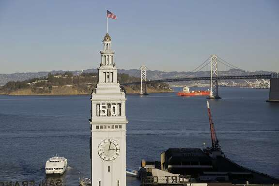 In this photo taken Wednesday, Dec. 16, 2015, is the Ferry Building in San Francisco. In the background is the San Francisco-Oakland Bay Bridge.  Atop the waterfront tower is the number 50 for the upcoming Super Bowl in February 2016. (AP Photo/Eric Risberg)