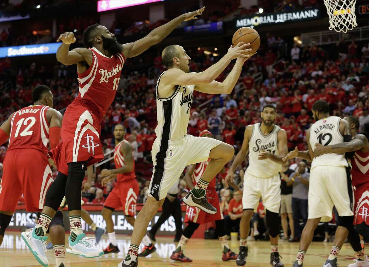 San Antonio Spurs guard Manu Ginobili (20) drivers past Houston Rockets guard James Harden (13) in the second half of an NBA basketball game Friday, Dec. 25, 2015, in Houston. Houston won 88-84. (AP Photo/Bob Levey)